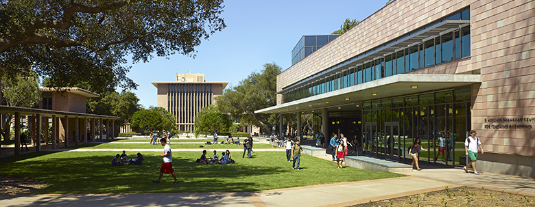 A diverse group of students walking to class and activities are framed by modern buildings on the Harvey Mudd College campus.